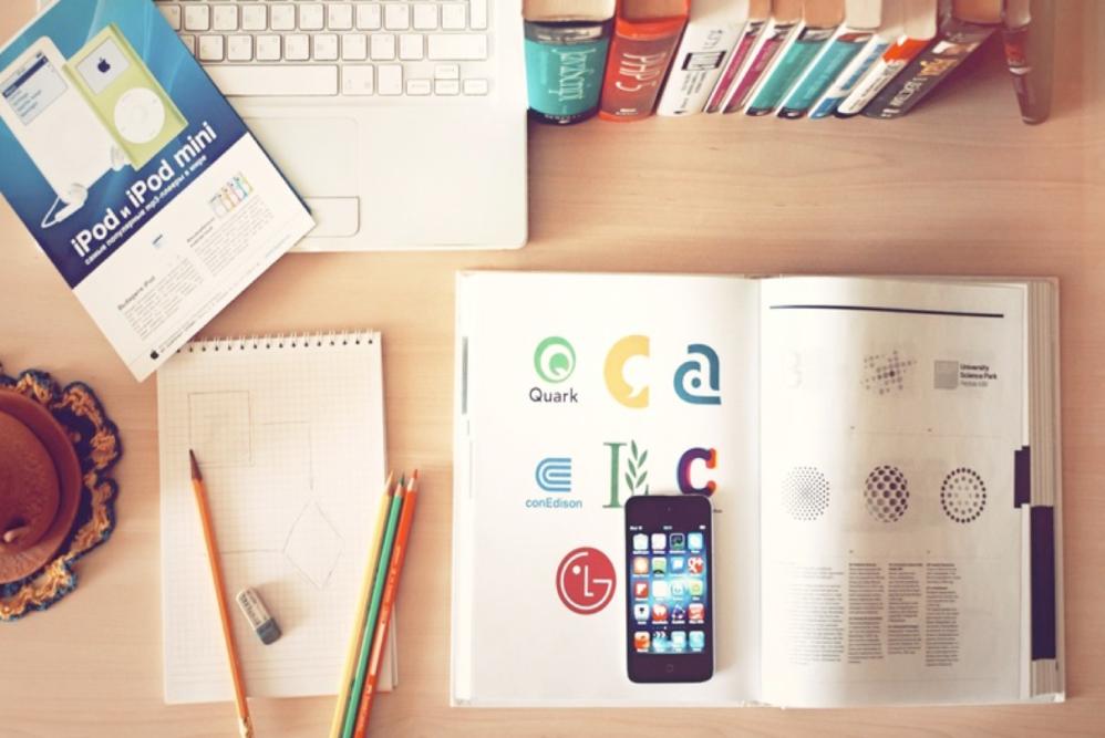 pöydän päällä iphone, kirjoja ja tietokone