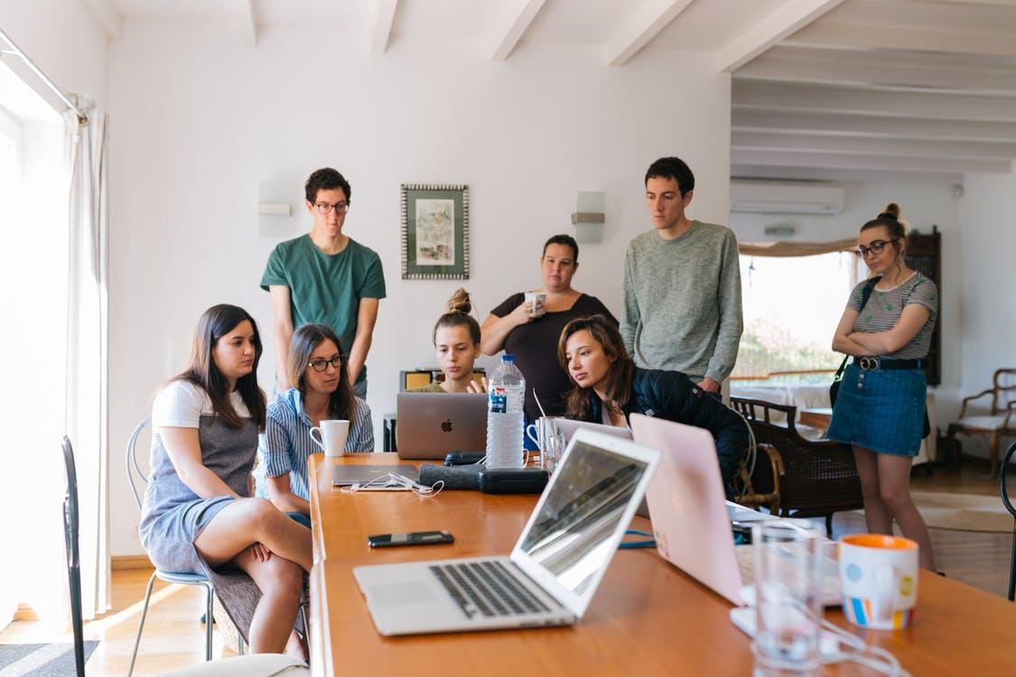 Somat kurssin etusivun kuva, jossa opiskelijat katsovat tietokonetta