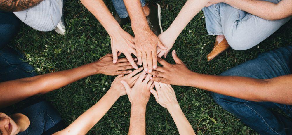 ihmiset yhdistävät kätensä